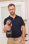 Handyman pointing power tool at camera — Stockfoto