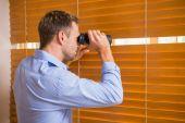 Man looking with binoculars through the blinds — Stok fotoğraf