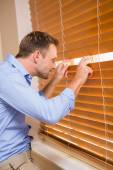 Curious man looking through the blinds — Stock Photo