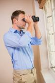 Man looking through a binoculars — Stock Photo