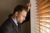 Serious businessman peeking through blinds — Stock Photo