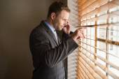 Businessman peeking through blinds — Stock Photo