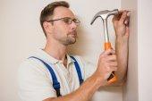 Handyman hammering nail in wall — Stock Photo