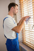 Manual worker cleaning blinds with a towel — Stockfoto