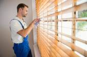 Handyman cleaning blinds with a towel — Stockfoto