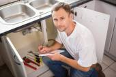 Plumber crouching and taking notes — Stockfoto