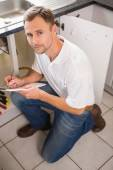 Plumber crouching and taking notes — Stok fotoğraf