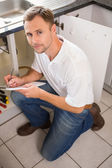 Plumber crouching and taking notes — Stock Photo
