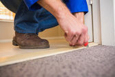 Handyman laying down a carpet — Stock Photo