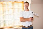 Handyman posing while holding a paintbrush — Stock Photo
