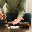 Man showing pills and holding beer bottle — Stock Photo #60966629