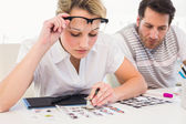 Editor using magnifying loupe to view the contact sheet — Stock Photo