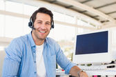 Portrait of a smiling photo editor wearing a headset — Stock Photo