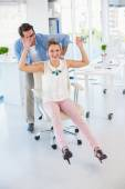 Creative business colleagues having fun on a swivel chair — Stock Photo