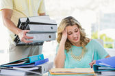 Stressed creative businesswoman with stack of files — Foto de Stock