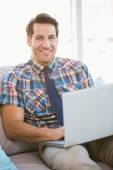 Portrait of man using laptop on couch — Stock fotografie