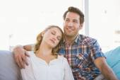 Girlfriend lying on the shoulder of her boyfriend on the sofa — Stockfoto