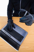 Mid section of a burglar using laptop and smartphone — Стоковое фото