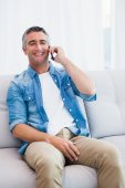 Smiling man sitting and phoning on the couch — Stock Photo