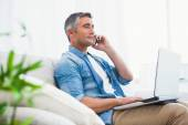 Cheerful man sitting on couch phoning and using laptop — Stock Photo