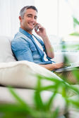 Happy man sitting on couch phoning and using laptop — Stockfoto