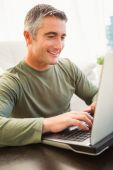 Smiling man with grey hair using laptop — Stock Photo