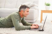 Smiling man lying on carpet using laptop — Стоковое фото