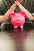 Mid section of a man with joined hands on piggy bank — Stock Photo