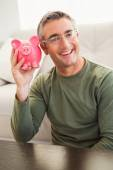 Smiling man posing with a piggy bank — Стоковое фото