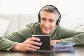 Smiling man listening music and holding cd — Stock Photo