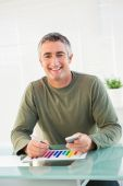 Smiling man analyzing chart and holding mobile phone — Stock Photo