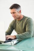 Concentrated casual man using laptop — Stock Photo