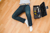 Man lying with a tools box near him — Stock Photo