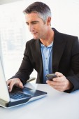 Businessman using laptop and holding smartphone — Stock Photo