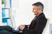 Cheerful businessman using laptop and relaxing — Stock Photo
