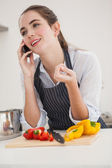 Pretty brunette on the phone while cooking — Stock Photo