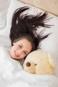 Pretty brunette under the duvet with teddy bear — Stok fotoğraf