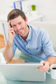 Smiling businessman using his laptop at desk — Stock Photo