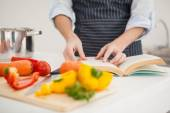 Woman following a recipe in book — Stock Photo