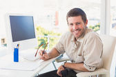 Smiling casual businessman at his desk — Stock Photo