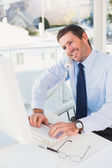 Smiling businessman working and phoning at his desk — Stock Photo