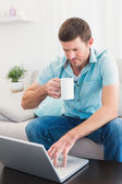 Concentrate man using his laptop at home — Stock Photo