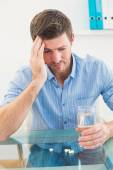 Hungover businessman holding glass of water and tablet  — Stock Photo