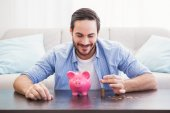 Smiling businessman putting coins into piggy bank — Foto de Stock