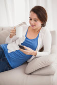 Pretty brunette sending a text on couch — Stock Photo
