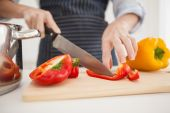 Woman slicing up red pepper — Stock Photo