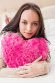Pretty brunette holding heart cushion on bed — Stock Photo