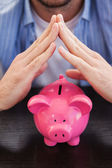 Casual man sheltering piggy bank — Stock Photo