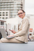 Young businesswoman using laptop holding her phone — Stock Photo