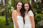 Pretty friends smiling at camera in white dresses — Stock Photo